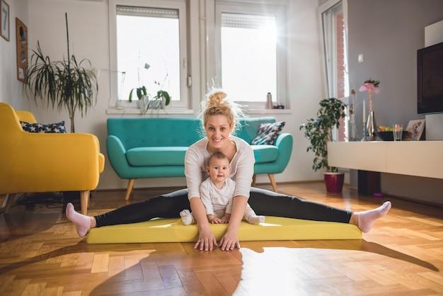 Madre ejercicio con su bebé en casa
