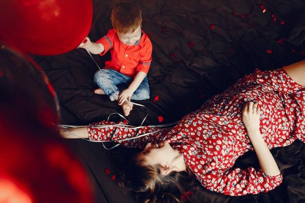 Madre elegante con pequeño hijo en una cama.