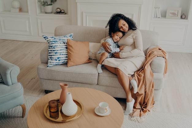 Madre embarazada africana soltera abrazando tiernamente a su pequeño hijo mientras está sentado en un sofá acogedor
