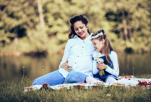 Madre embarazada e hija pequeña haciendo un picnic en el parque en un día soleado. la foto tiene un espacio vacío para tu texto