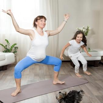 Madre embarazada haciendo entrenamiento de yoga de diversión con su niña de cabrito y mascota jugando en casa