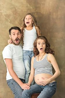 Madre embarazada con hija adolescente y esposo. retrato de estudio familiar sobre pared marrón