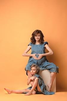 Madre embarazada con hija adolescente. retrato de estudio familiar sobre pared marrón