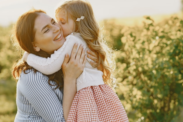 Madre embarazada con su hija en un campo
