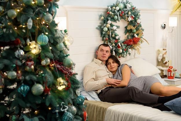 Madre embarazada y su marido en casa con adornos navideños.