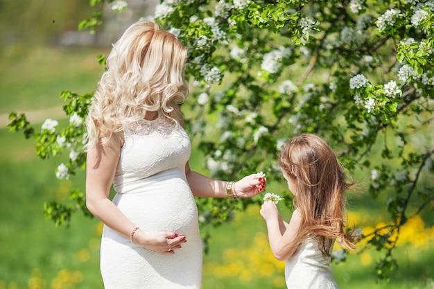 Madre embarazada y su pequeña hija se divierten al aire libre. retrato de mirada familiar