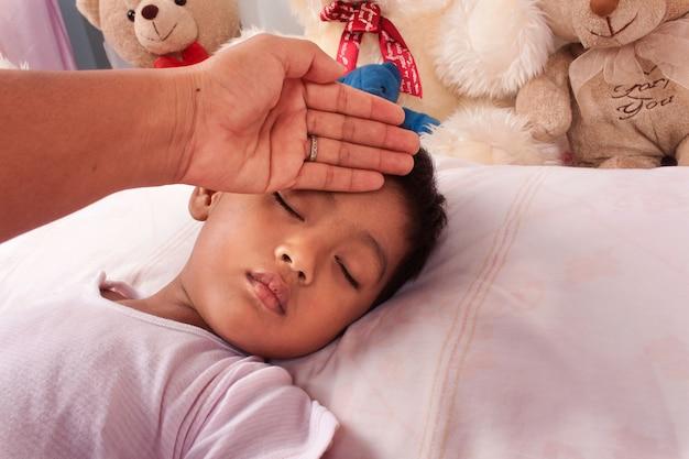 Una madre enferma de un pequeño muchacho asiático cuida