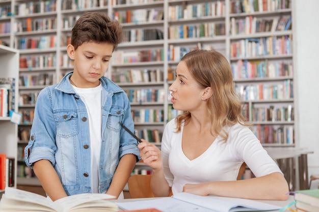 Madre enojada regañando a su hijo en la biblioteca