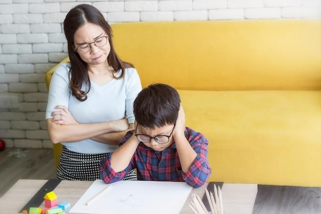 Madre está enojada con su hijo haciendo la tarea