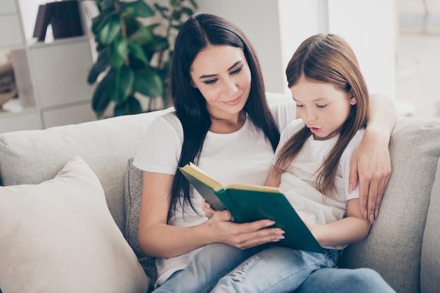 Madre enseña a su hija a leer el libro en la sala de la casa