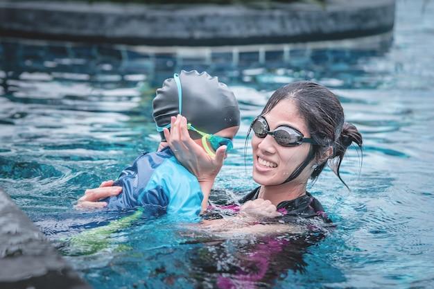 Madre le enseña a su hijo a nadar