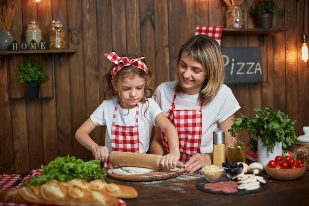 Madre enseñando a hija cocinando pizza y sonriendo