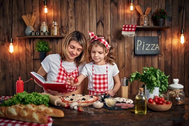 Madre enseñando a hija cocinando pizza
