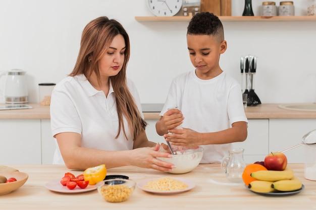 Madre enseñando a hijo a preparar comida