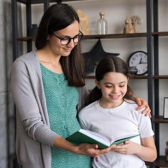 Madre enseñando a niña a leer