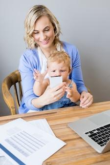 Madre enseñando a su bebe el teléfono móvil