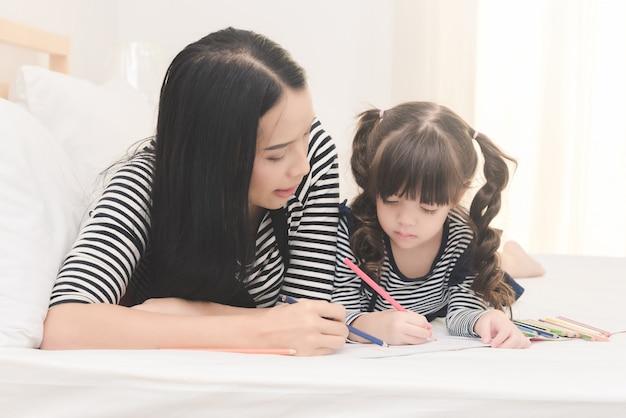 Madre enseñando a su hija hija a estudiar en casa.