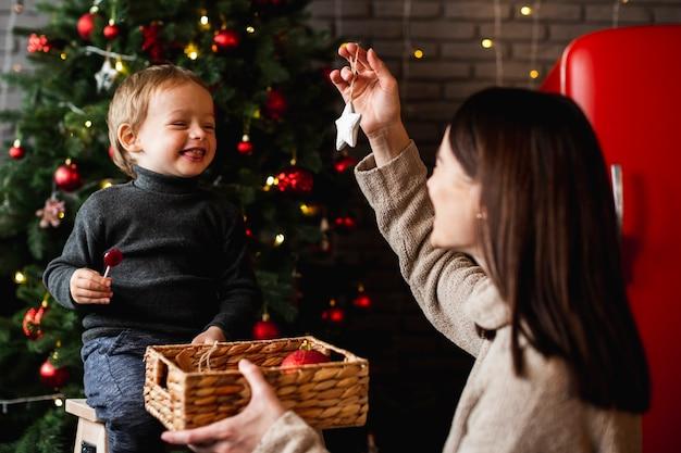 Madre enseñando a su hijo a decorar el árbol de navidad