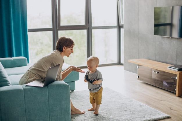 Madre eorking en la computadora portátil mientras su hijo juega juegos de video