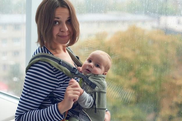 Madre con ergobaby llevar niño en casa.