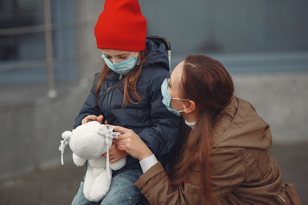 Una madre europea en un respirador con su hija está parada cerca de un edificio. el padre le está enseñando a su hijo cómo usar una máscara protectora para salvarse del virus.