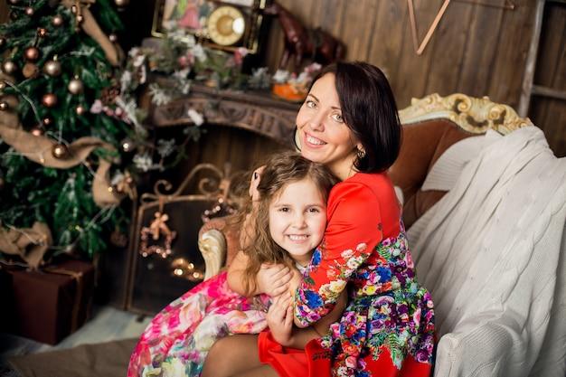 La madre feliz abraza a la hija en la noche de navidad mágica.