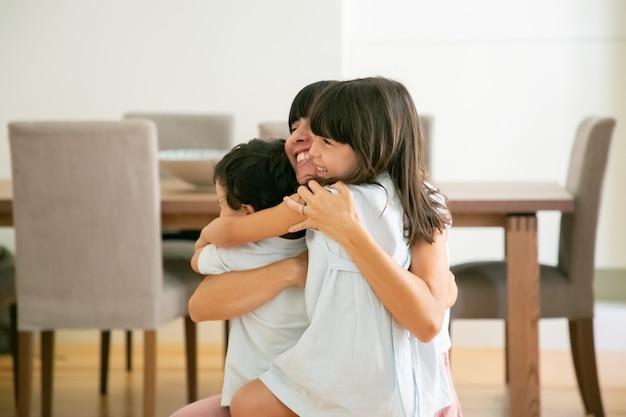Madre feliz abrazando a sus adorables hijos con ambas manos.