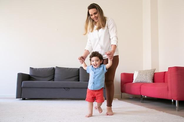 Madre feliz cogidos de la mano del hijo y enseñándole a caminar. alegre niño rizado de raza mixta caminando descalzo sobre una alfombra con la ayuda de una mamá de pelo largo. tiempo en familia, infancia y concepto de primer paso.