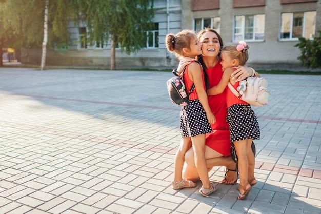 Madre feliz conociendo a sus hijas después de clases