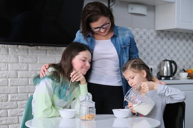 Madre feliz cuidando a sus hijas en la cocina