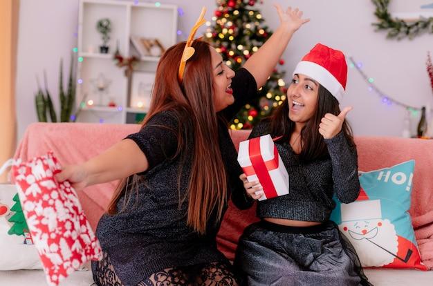 Madre feliz con diadema de reno sostiene una bolsa de regalo manteniendo los brazos abiertos y mira a la hija emocionada con sombrero de santa sosteniendo una caja de regalo y apuntando hacia arriba sentado en el sofá disfrutando de la navidad en casa