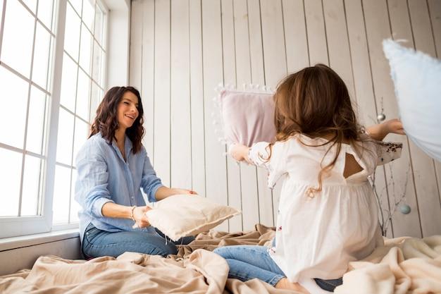 Madre feliz e hija jugando con almohadas