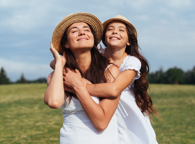 Madre feliz e hija posando en la naturaleza
