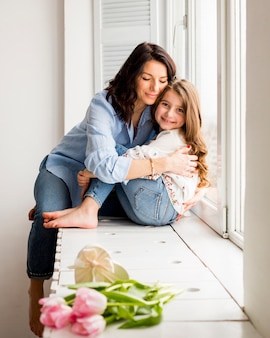 Madre feliz e hija que abrazan en travesaño de la ventana