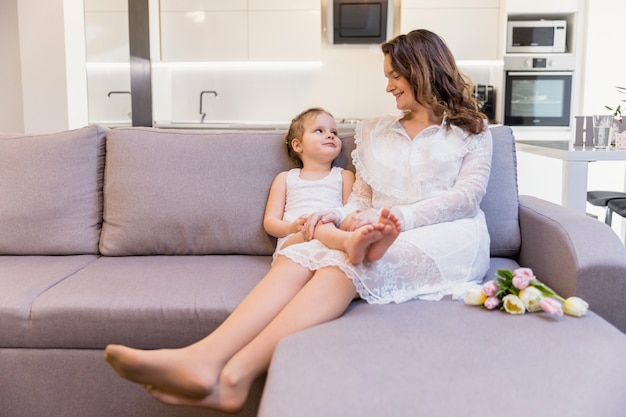 Madre feliz e hija que se miran que se sientan en el sofá en casa