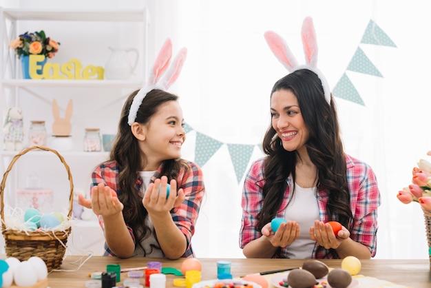 Madre feliz e hija que sostienen los huevos de pascua a mano que se miran en casa
