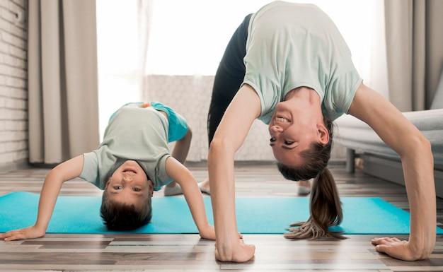Madre feliz de entrenar con hijo en casa