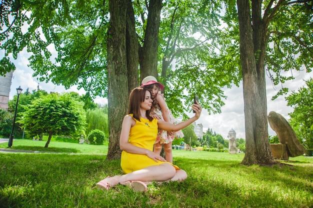 Madre feliz haciéndose una foto con su hija en el parque