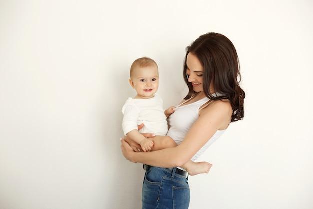 Madre feliz hermosa joven que sonríe riendo deteniendo a su hija del bebé sobre la pared blanca.