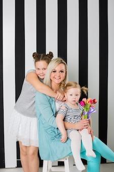 Madre feliz con hijas y ramo de flores.
