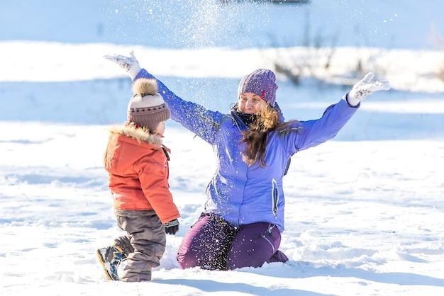 Madre feliz con hijo jugando en el parque de nieve de invierno.