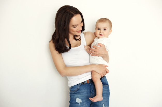 Madre feliz joven que sonríe sosteniendo mirar a su hija del bebé sobre la pared blanca.