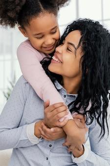 Madre feliz jugando en casa con su hija