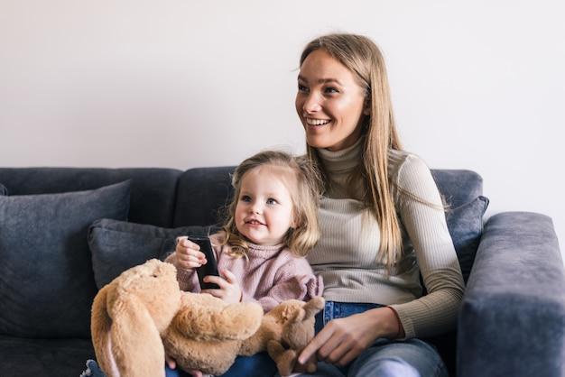 Madre feliz con linda hijita viendo televisión usando el control remoto