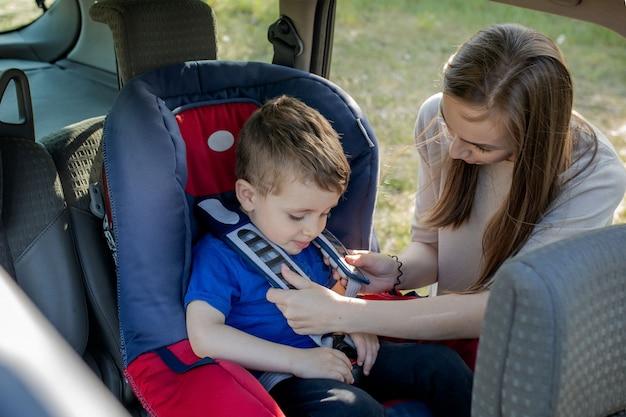 Madre feliz mirando a su hijo en un asiento de bebé. mujer joven preparando a un niño para un viaje. concepto de conducción de seguridad.