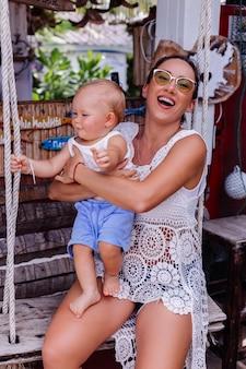 Madre feliz con niño en columpio