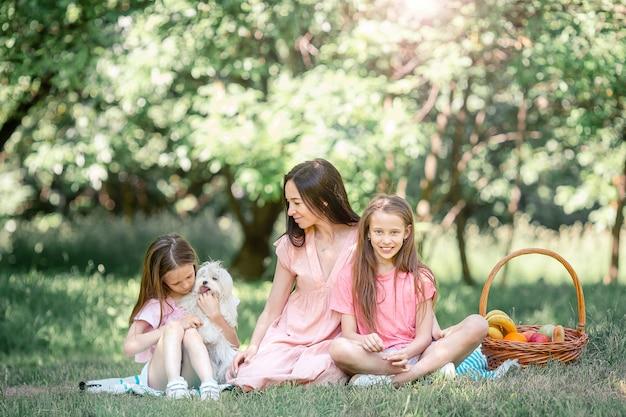 Madre feliz y pequeñas hijas se relajan junto al lago
