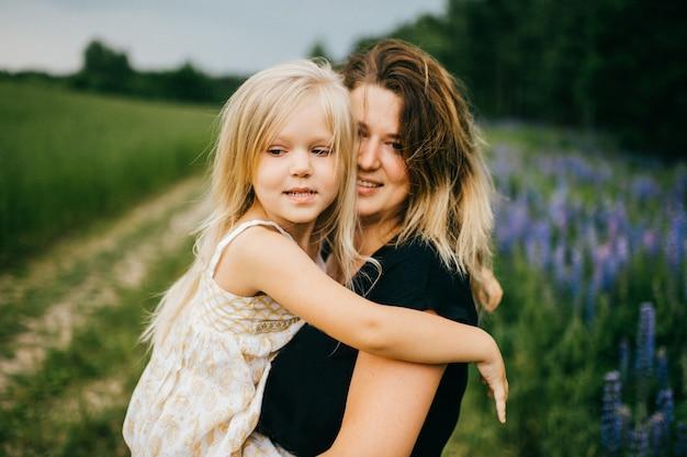 Madre feliz que abraza a su pequeña hija rubia sonriente hermosa en campo del verano.