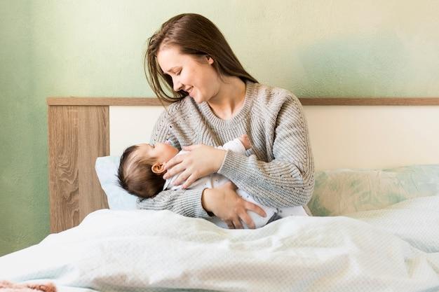 Madre feliz que celebra al bebé en brazos en cama