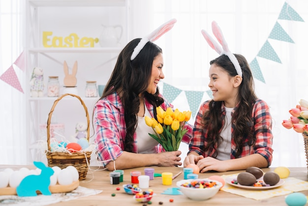 Madre feliz que celebra el ramo de los tulipanes que mira a su hija con los huevos de pascua en la tabla